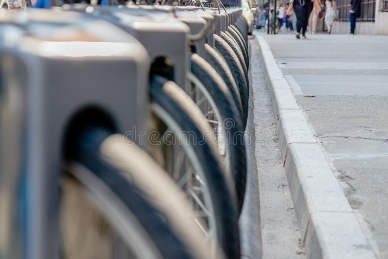 Close-up of bike tire parked in bikes docking station. Row of bikes for rent at docking stations in New York, USA stock photo