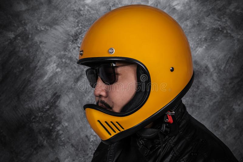 Close up of biker man in motorcycle helmet and leather jacket. Close up of biker man in motorcycle helmet and black leather jacket stock photo