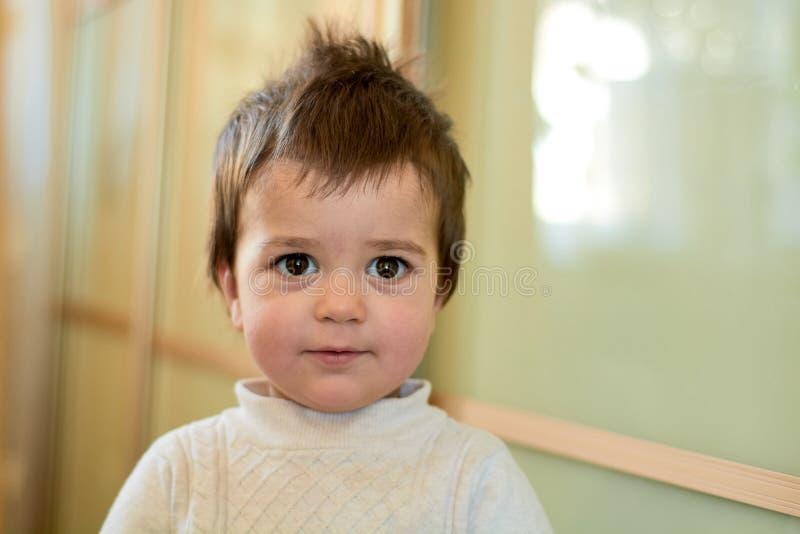 Close-up binnenportret van een babyjongen met ongehoorzaam haar De diverse emoties van een kind stock afbeeldingen