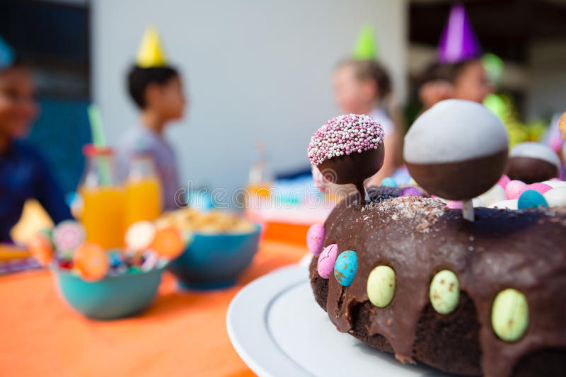 Close up of birthday cake with children in background. During party royalty free stock image