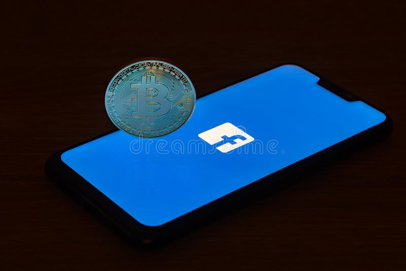 Bitcoin coin with the Facebook logo on a smartphone screen royalty free stock image