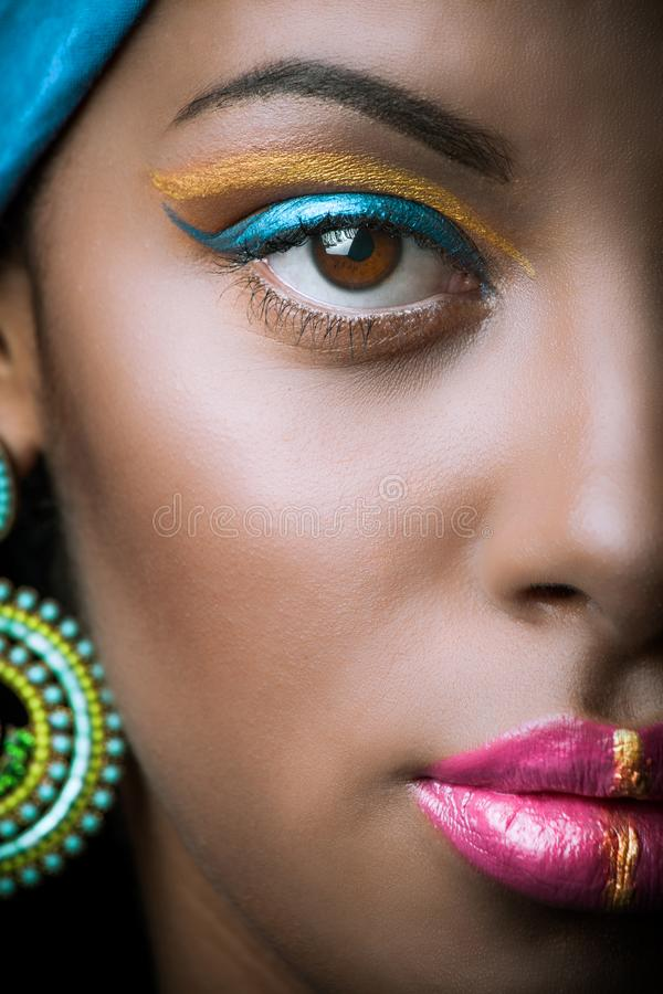 Close up of black African woman face with golden and blue makeup royalty free stock photo