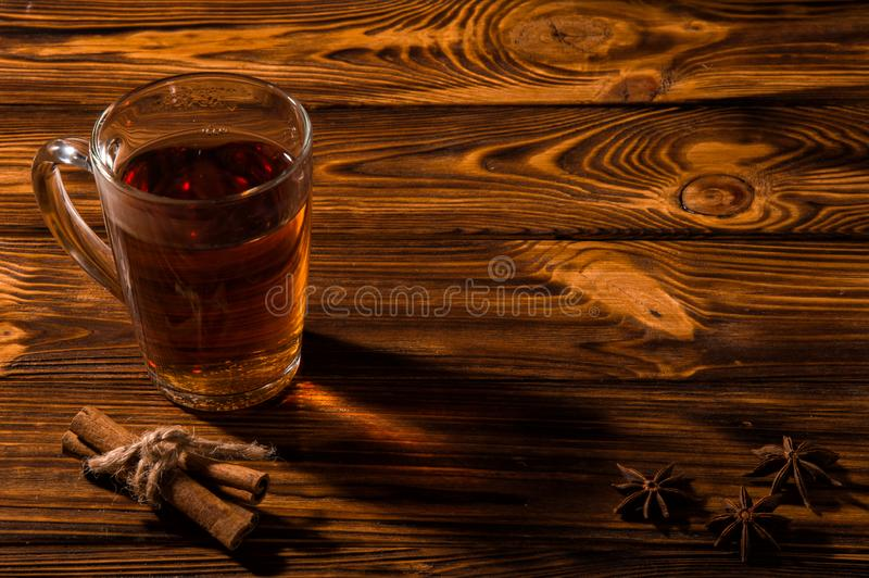 Close up. Black aromatic tea in a glass transparent cup. Cinnamon sticks tied with twine. Copy space royalty free stock image