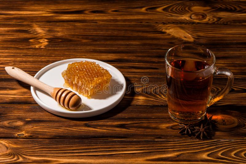 Close up. Black aromatic tea in a glass transparent cup. White plate with gold honey on a Rustic brown wooden table royalty free stock images