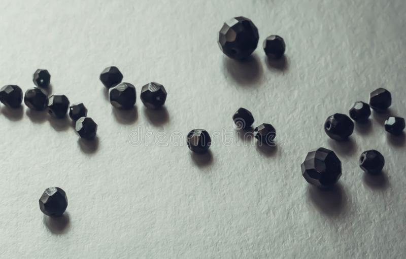 Close-up of black beads on grey background. Onyx semi-precious stone stock photography