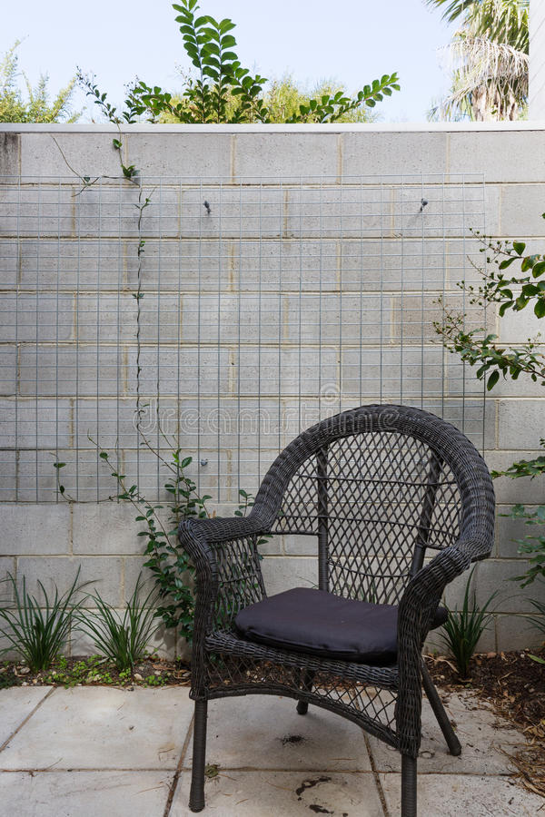 Close up of black cane outdoor chair in courtyard against block stock photos
