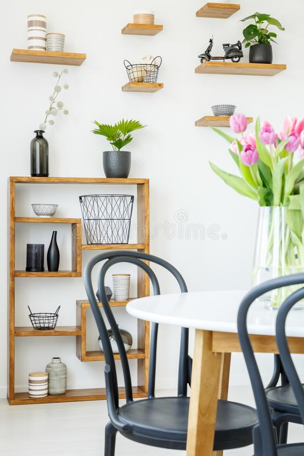 Close-up of a black chair and white table with tulips, and decor royalty free stock images