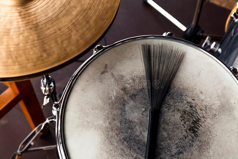 Close-up of of black drum brush on a white shabby drum and а part of golden cymbal. Concept concert, live music, performance, stock photos