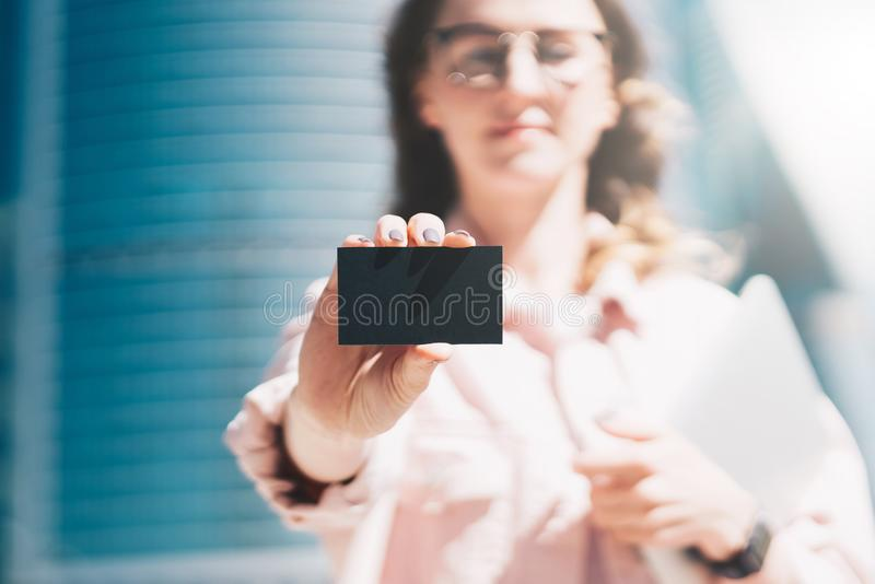 Close-up of black empty credit, business, calling, visiting card in hand of young businesswoman, standing outdoors. Female hand holds pasteboard. Focus on blank stock image