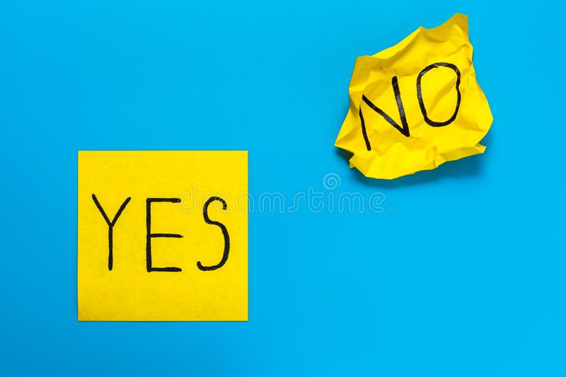 Close up black handwritten inscription yes and no word on two yellow square stickers on blue background with copy spase, royalty free stock image