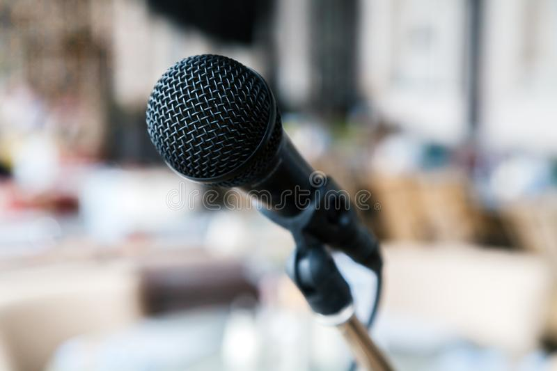 Close-up black iron microphone stands on the stage. Live music concert in a restaurant or bar in the evening royalty free stock photo