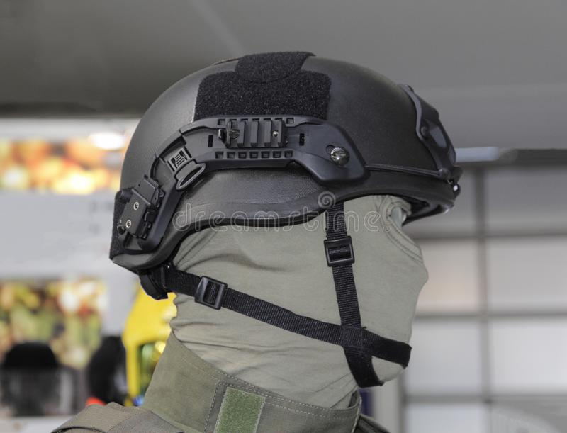 Black military combat helmet from side. The close up of black military combat helmet from profile on the doll stock images
