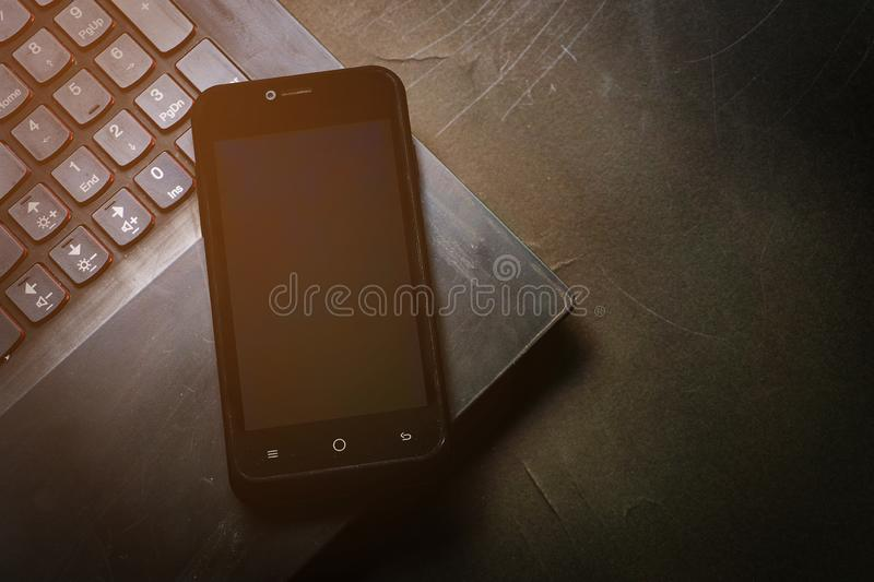 Close up black mobile phone on black laptop on desk background in dramatic lighting tone. Concept for business, planning or diary. royalty free stock photo