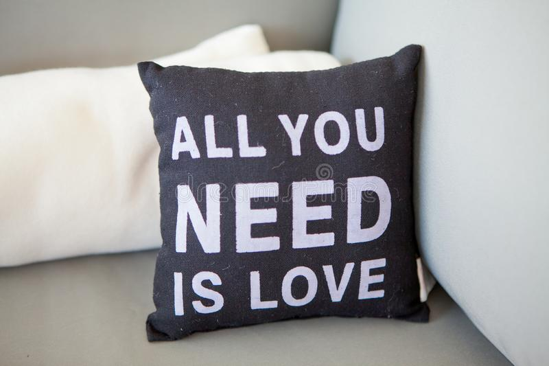 Close-up black pillow with an inscription all you need is love on a light couch with pillows, selective focus royalty free stock photos