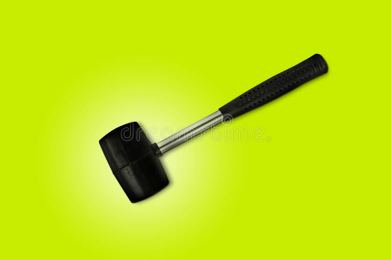 Close up black rubber mallet isolated on bright green background. Rubber hammer is a construction tool. Clipping path royalty free stock photography