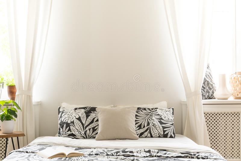 Close-up of black and white flower design pillows on a bed. Lace curtains on the sides of a headboard in a bright bedroom interior stock photography