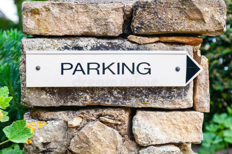 Close-up black and white signpost arrow with parking on a brown stone old pillar. Concept signpost for parking in a french villa, stock image