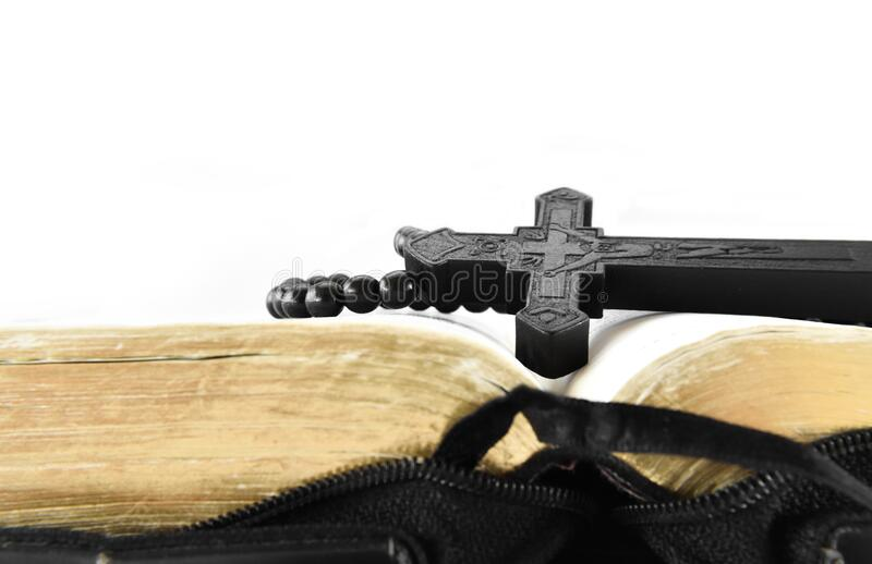 Close-up of black wooden Christian cross on holy Bible.  stock image