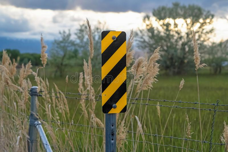 Close up of black and yellow diagonal stripes road sign beside barbed wire fence royalty free stock image
