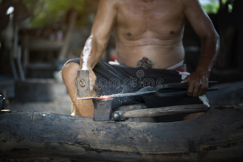Blacksmith manually forging the molten metal on the anvil. Close up blacksmith manually forging the molten metal on the anvil royalty free stock image
