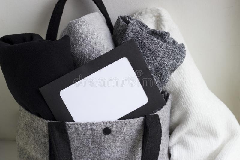 Close-up blank frame and rolled clothes in woolen gray bag on white background. Black, grey and white textiles. Monochrome concept. Copy space for text royalty free stock photo
