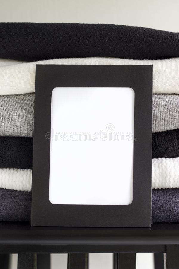 Close-up blank frame and stack of folded clothes on white background wall. Black, grey and white textiles. Copy space for text. Monochrome concept stock photography