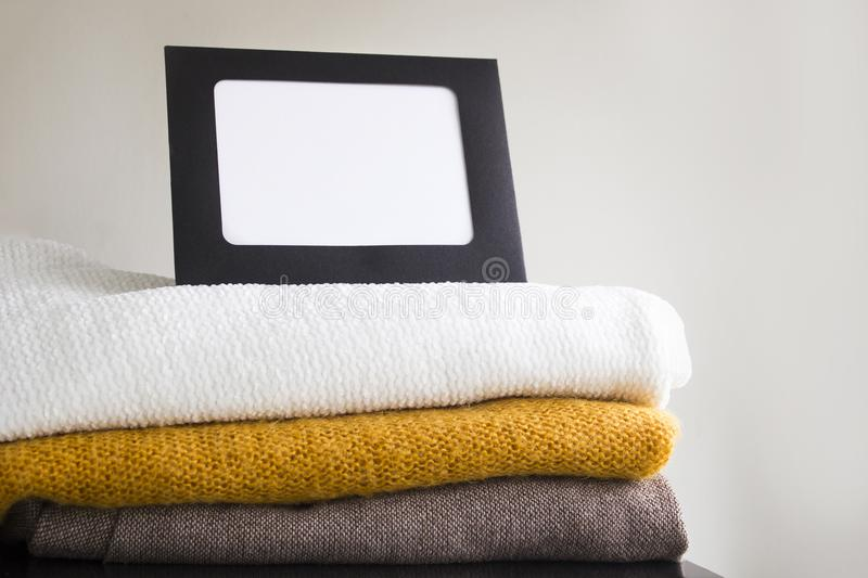 Close-up blank frame and stack of folded clothes on white background wall. Multicolored knitted textiles. Concept with copy space for text stock images