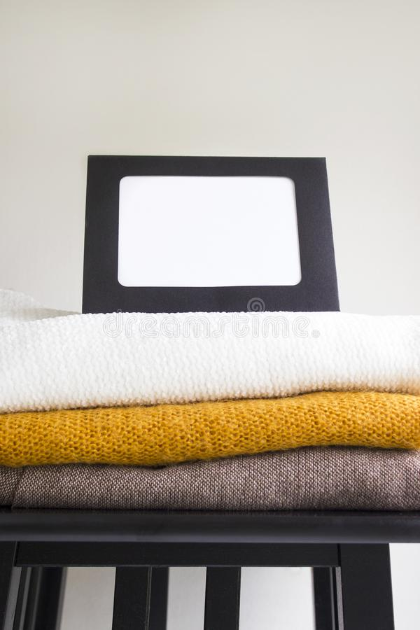 Close-up blank frame and stack of folded clothes on white background wall. Multicolored knitted textiles. Concept with copy space for text royalty free stock photo