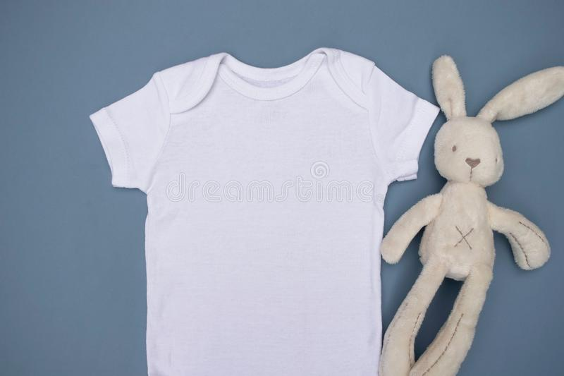 Close up of blank white baby bodysuit grow mockup with cream rabbit soft toy on a light blue background royalty free stock images