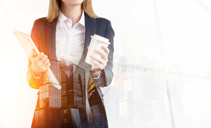 Close up of blond woman with coffee and notebook in misty city royalty free stock image