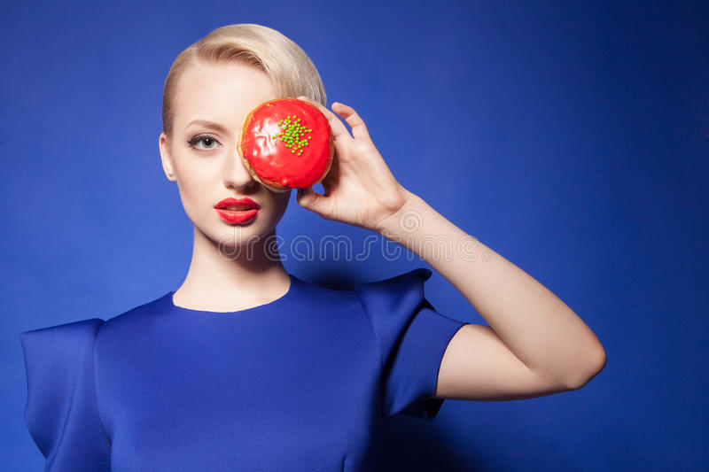 Close-up of blonde-haired model with red donut covering eye royalty free stock images
