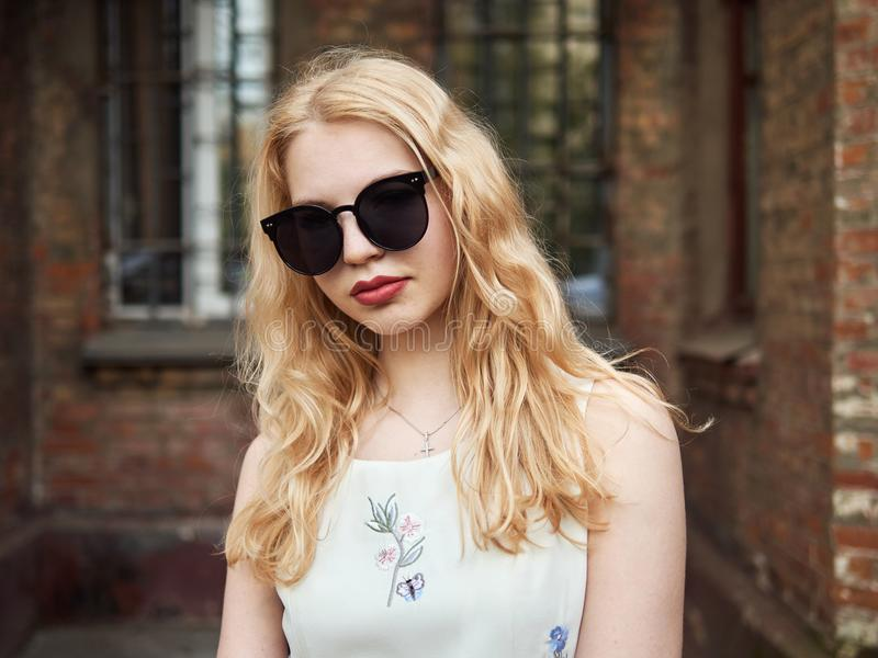 Close up of blonde student girl in trendy sunglasses posing against brick wall, enjoying warm sun light, recreation and relaxation royalty free stock photo