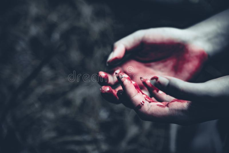 Close up of bloody hands in dark forest background. Horror and g. Host concept. Criminal and murder concept. Halloween day and sacrifice theme. People and royalty free stock image