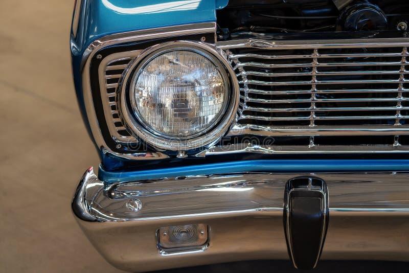 Close Up Of Blue Classic Car Headlight. Close up of blue classic car front, headlight, grill and bumper stock photos