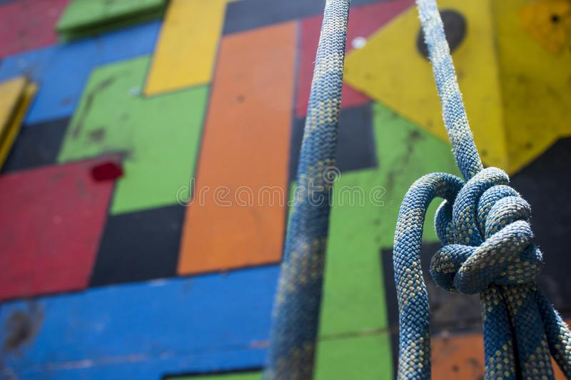 Close-up of a blue climbing knot hanging in front of a colorful gym climbing wall. stock photo