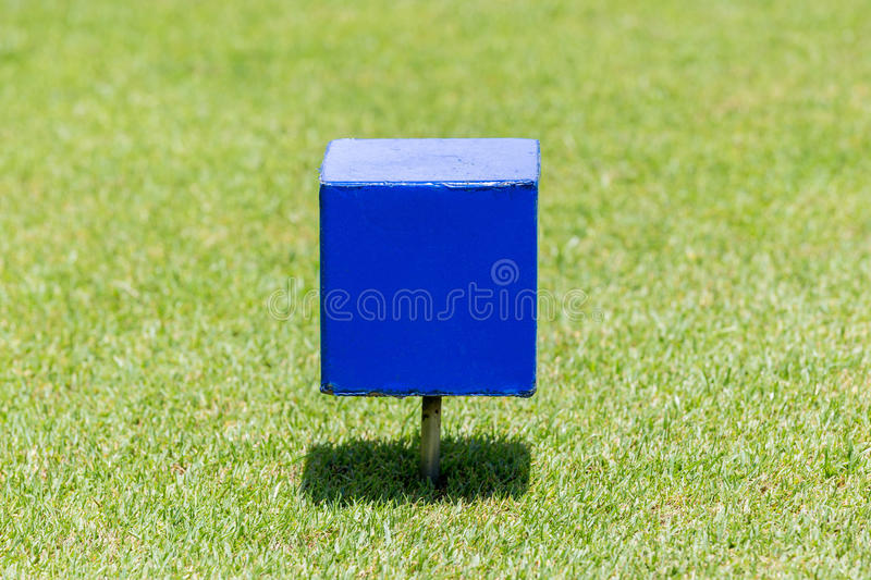 Close-up blue color wooden tee off area or tee box with blurred. Natural green golf course in background royalty free stock photo