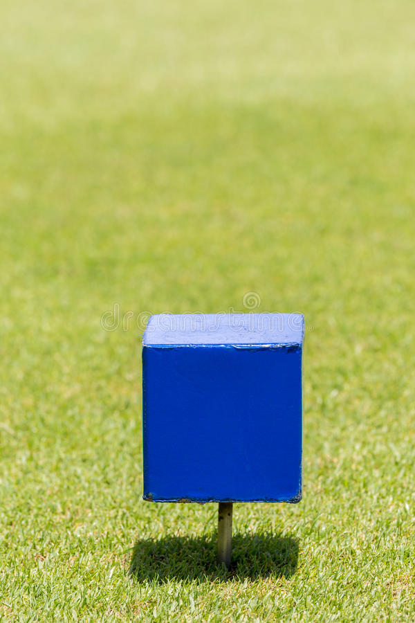 Close-up blue color wooden tee off area or tee box with blurred. Natural green golf course in background royalty free stock image