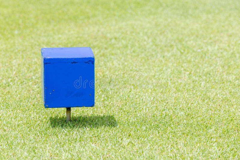 Close-up blue color wooden tee off area or tee box with natural. Green golf course in background stock photography