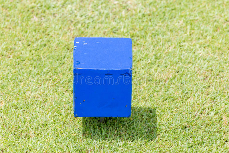 Close-up blue color wooden tee off area or tee box with natural. Green golf course in background royalty free stock photo
