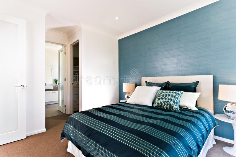 Close up of a blue decorative bedroom to an entrance. Close up of a blue decorative bedroom with an entrance and white walls beside the glossy blanket and royalty free stock photography
