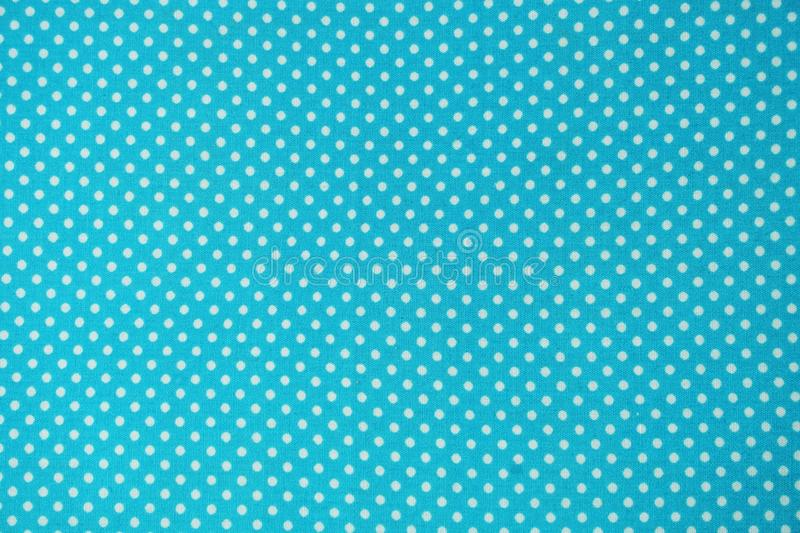 Close up of blue fabric with white polka dot pattern stock illustration