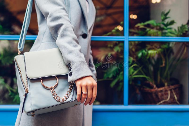 Close-up of blue female handbag. Woman holding leather bag outdoors. Fashionable accessories. And clothes stock photo