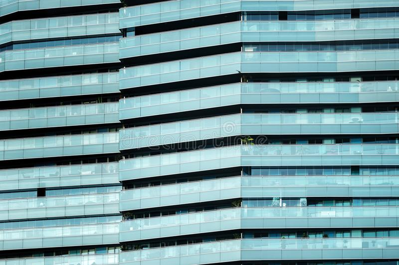 Close-up of a modern-looking glass facade. Close-up of the blue glass facade of a modern building, the horizontal lines draw an interesting pattern to use as royalty free stock photos