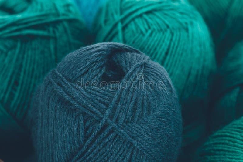 Warm yarn balls in wicker basket. Close up of blue and green knitting yarn balls stock image