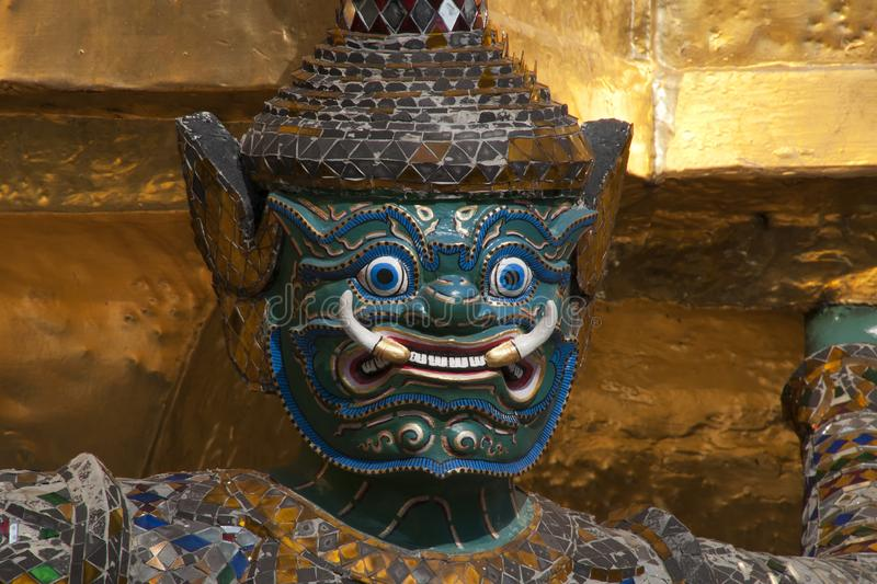 Close-up of blue and green mask of a mirrored demon holding up golden chedhi stock images