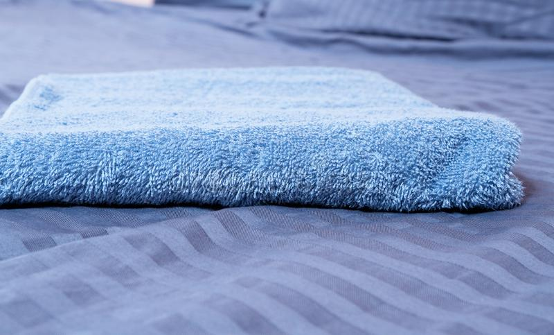 Close up of Blue inn linens and bath towel lying on bed. Hotel service and clean bedroom background. House room and home textile. Copy space and template royalty free stock photo