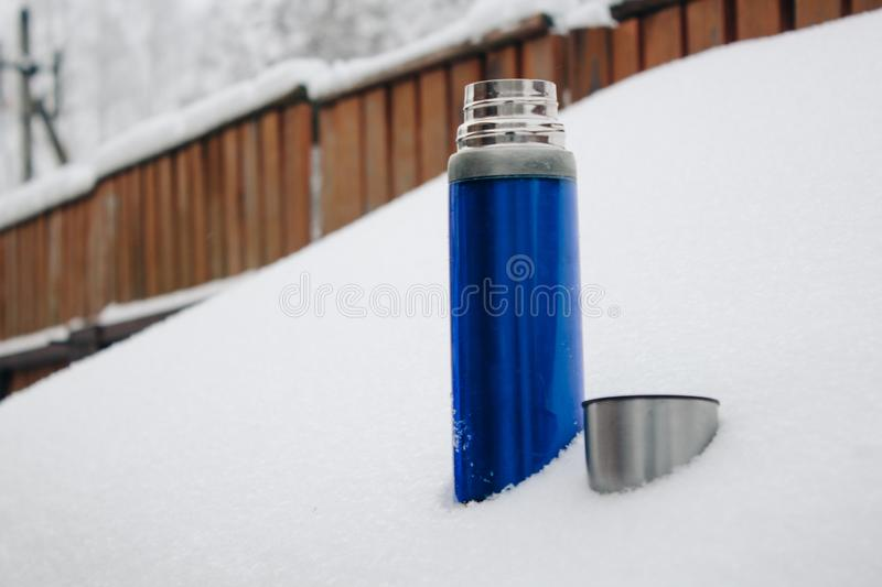Close-up blue silver thermos with coffee or tea in snow in back yard. Winter holidays, hot drinks concept stock photography