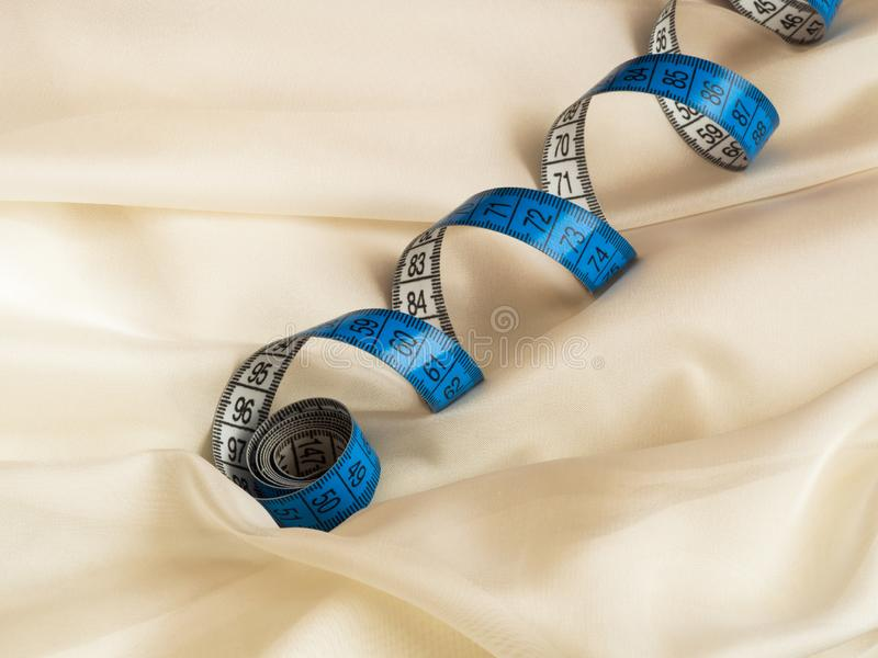 Close up of blue twisted tape measure on cream tulle with drapery stock photos