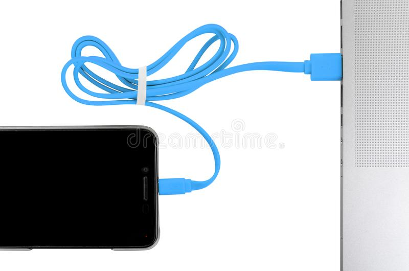 Close-up blue usb cable connect phone and laptop computer new technology concept. Horizontal frame royalty free stock photos