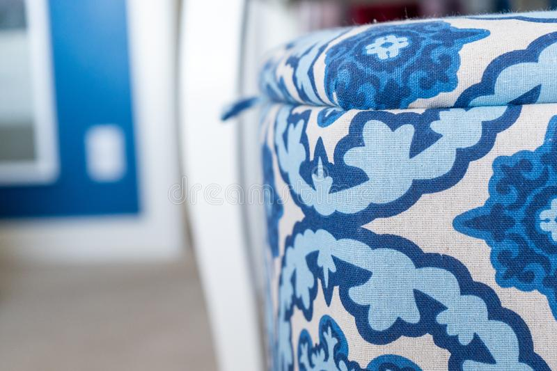 Close up of a blue and white fabric laundry basket a decorative storage box with a lid, in a bedroom with blue and white stock image